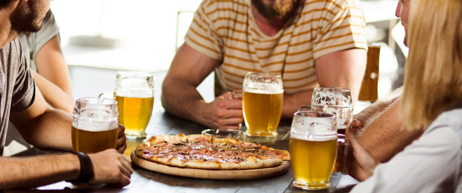 group of young people eating pizza and drinking beer