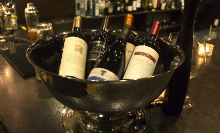wine bottles in a bowl on the bar