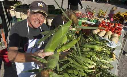 man holding corn at the farmers market