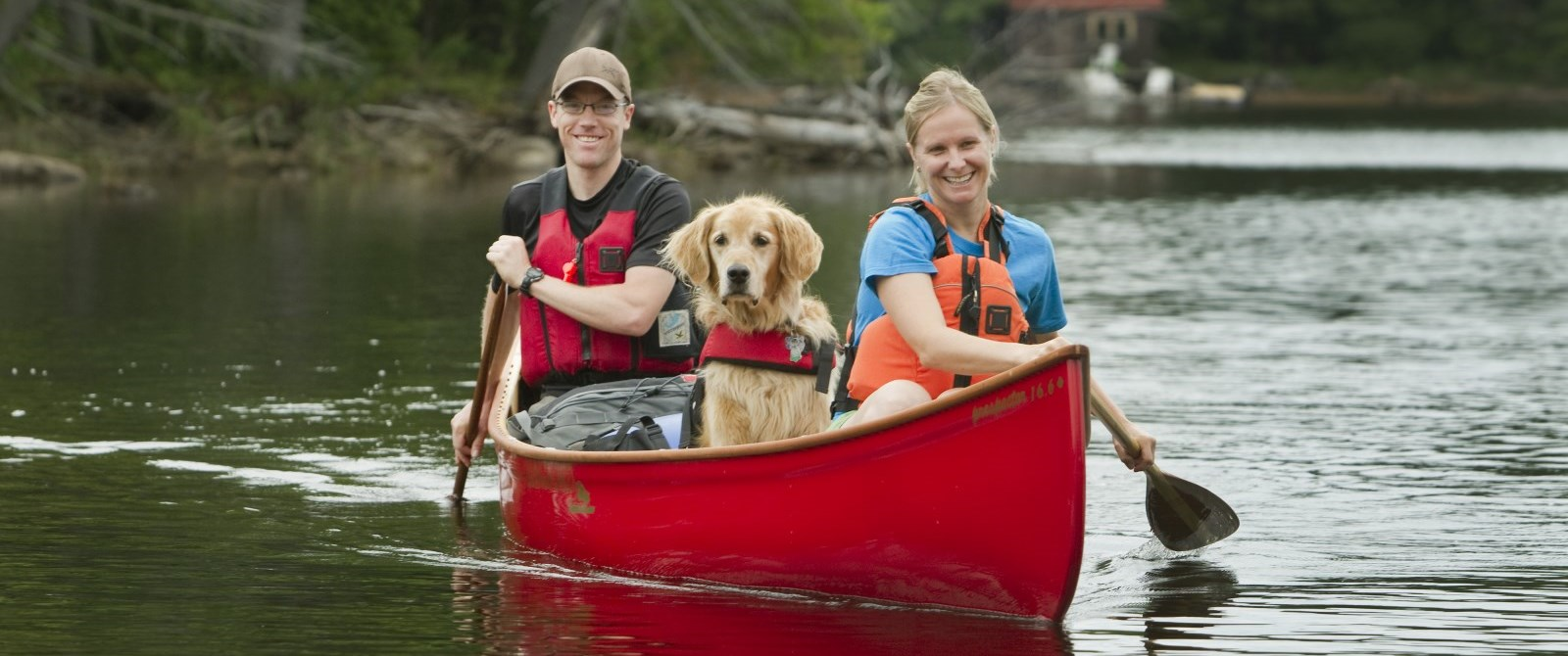 canoe with 2 people and a dog in it