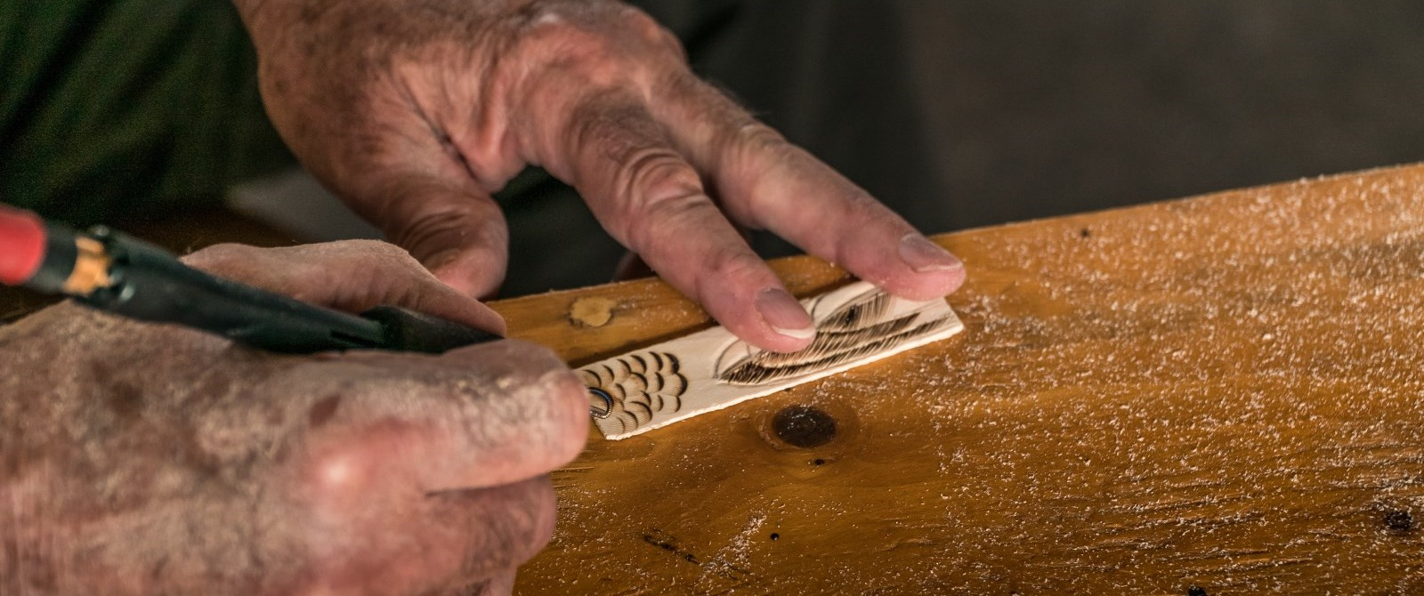 hands carving a piece of wood
