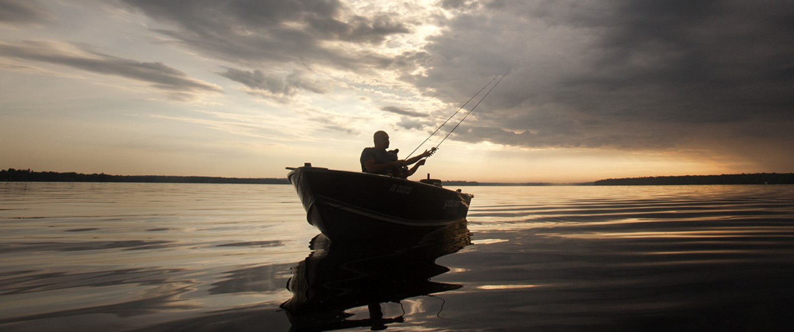Fishing in boat at sunset