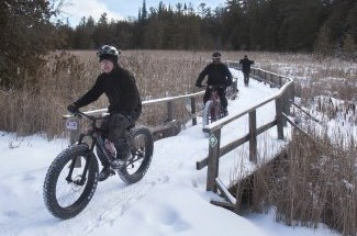 three people winter fat biking on the trail