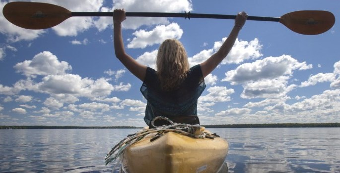 woman in kayak with paddle above her head