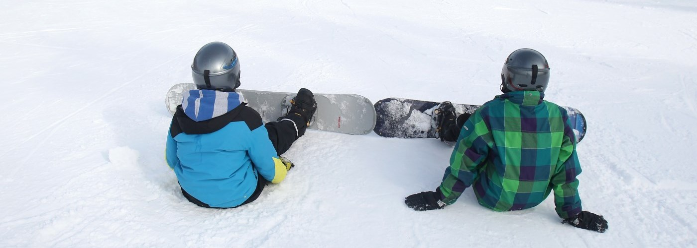 snowboarders sitting on hill